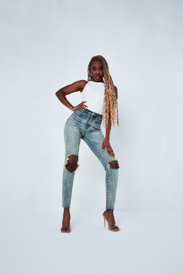 Model wearing light blue skinny denim jeans with rips