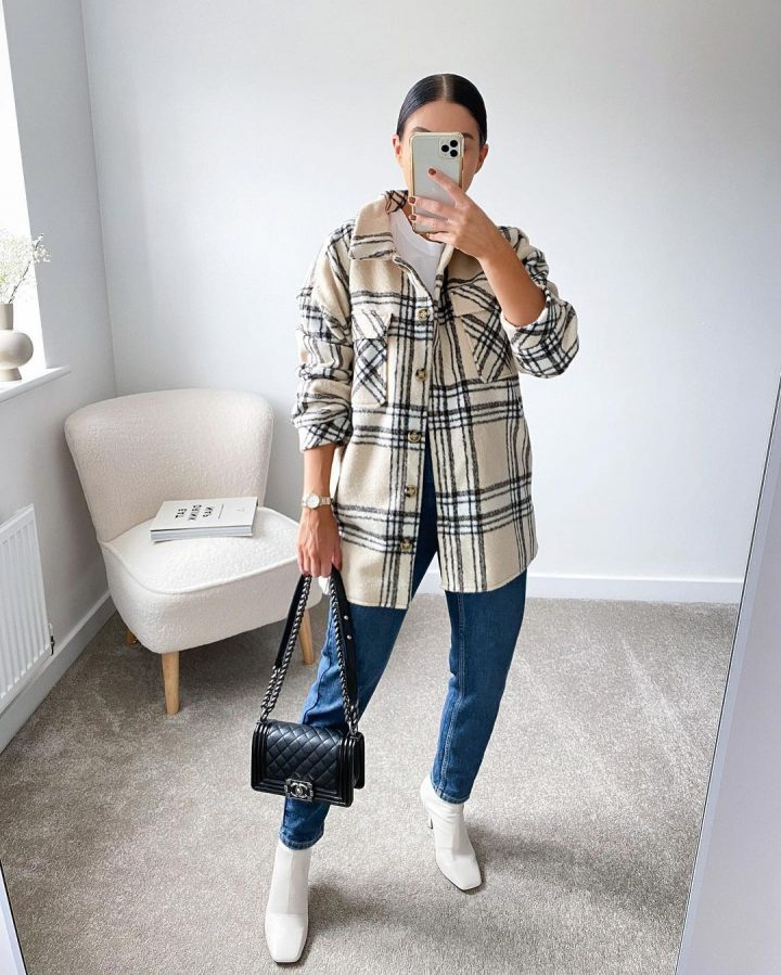 girl wearing checked shacket taking photo in the mirror