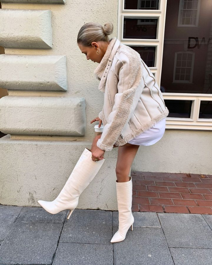 Girl wearing cream jacket with knee high croc boots