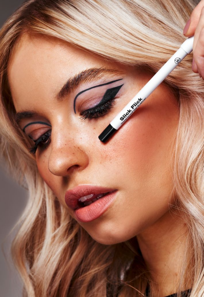 blonde model holding missguided beauty eyeliner to face