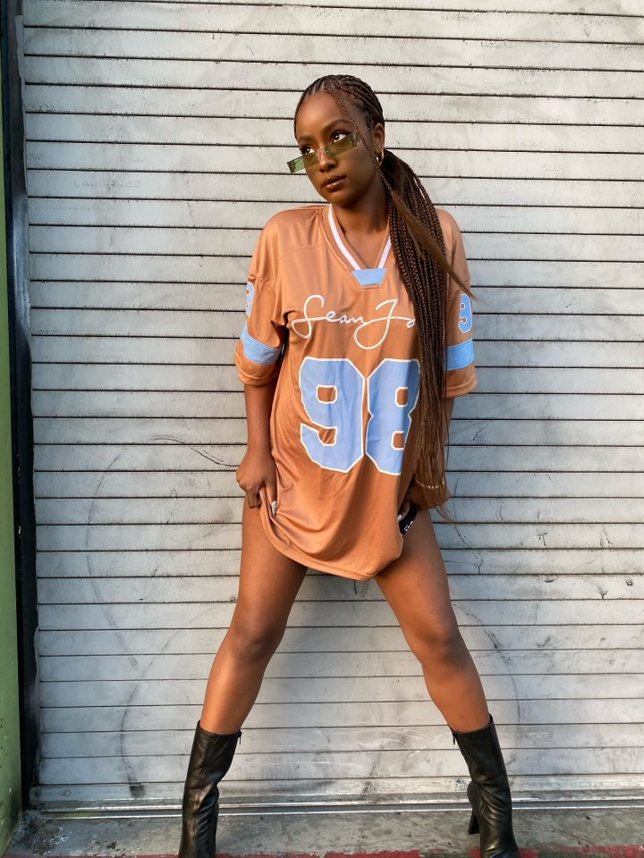 Girl standing against wall wearing sean john x missguided oversized t shirt