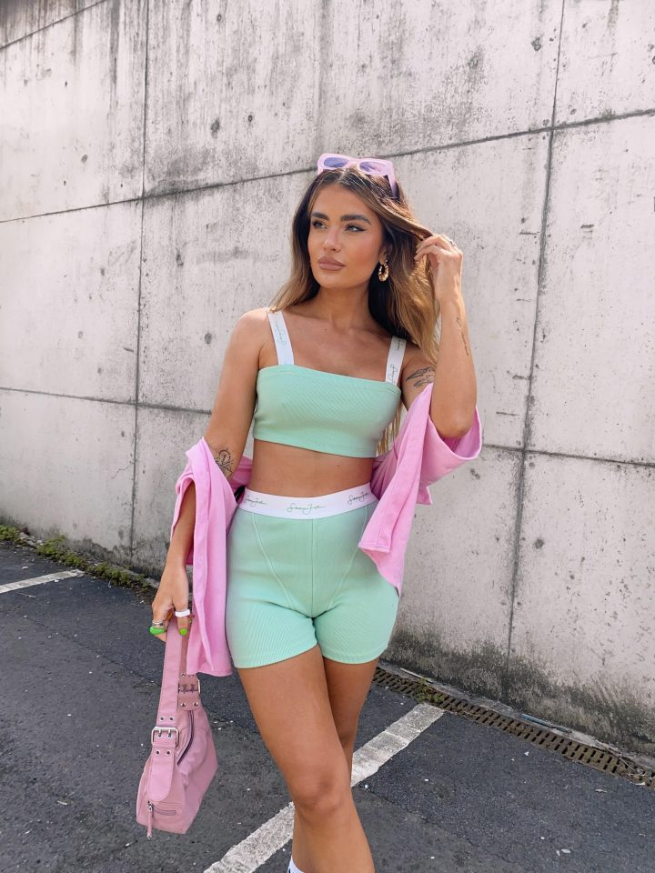 girl wearing pink and green in car park