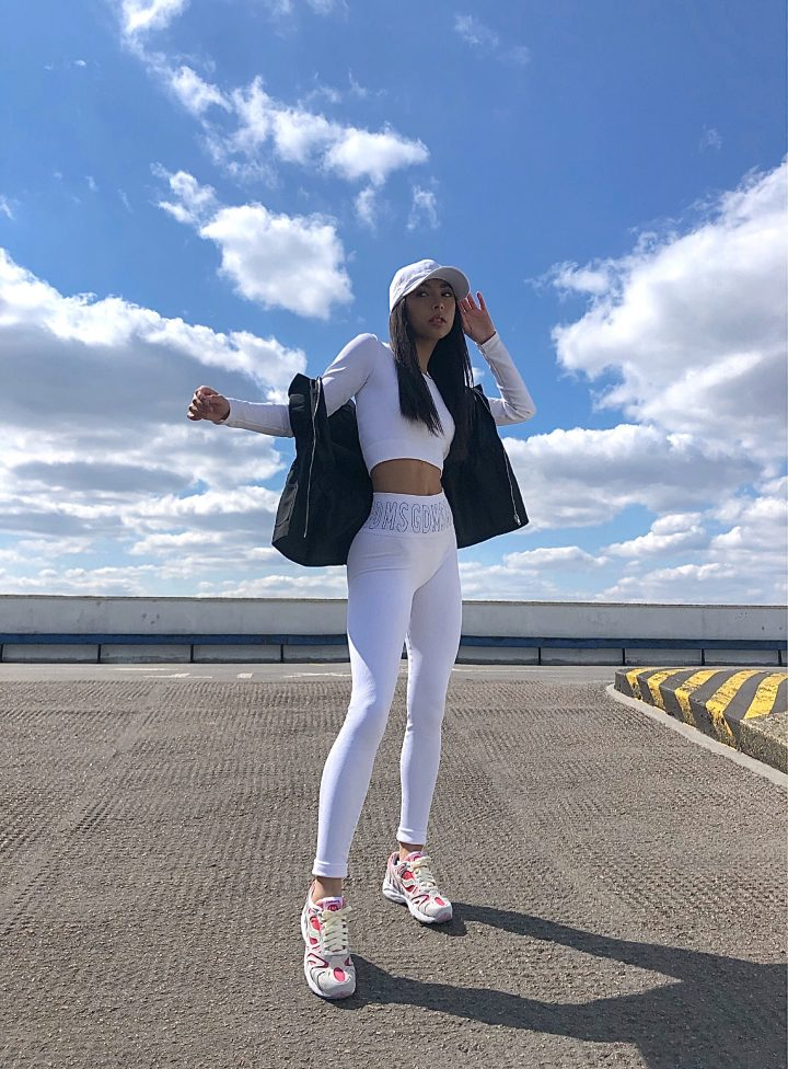 girl wearing gym sets stood on roof